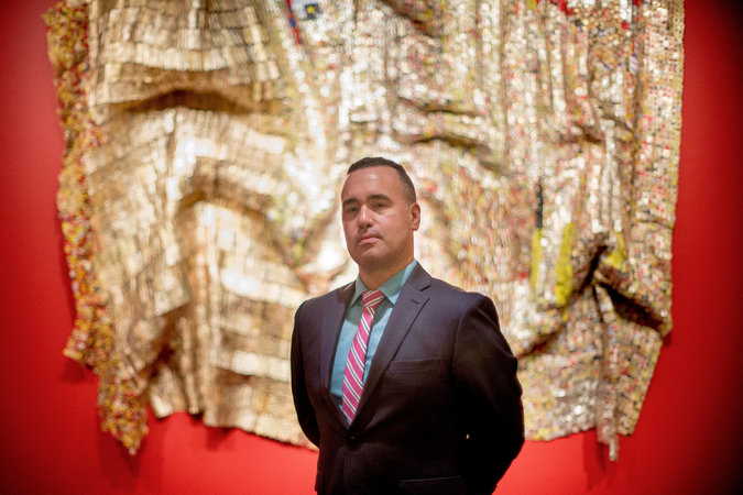 Kevin Dumouchelle with an untitled 2009 work by El Anatsui at the Smithsonian Museum of African Art in Washington. Image courtesy of Gabriella Demczuk for The New York Times.
