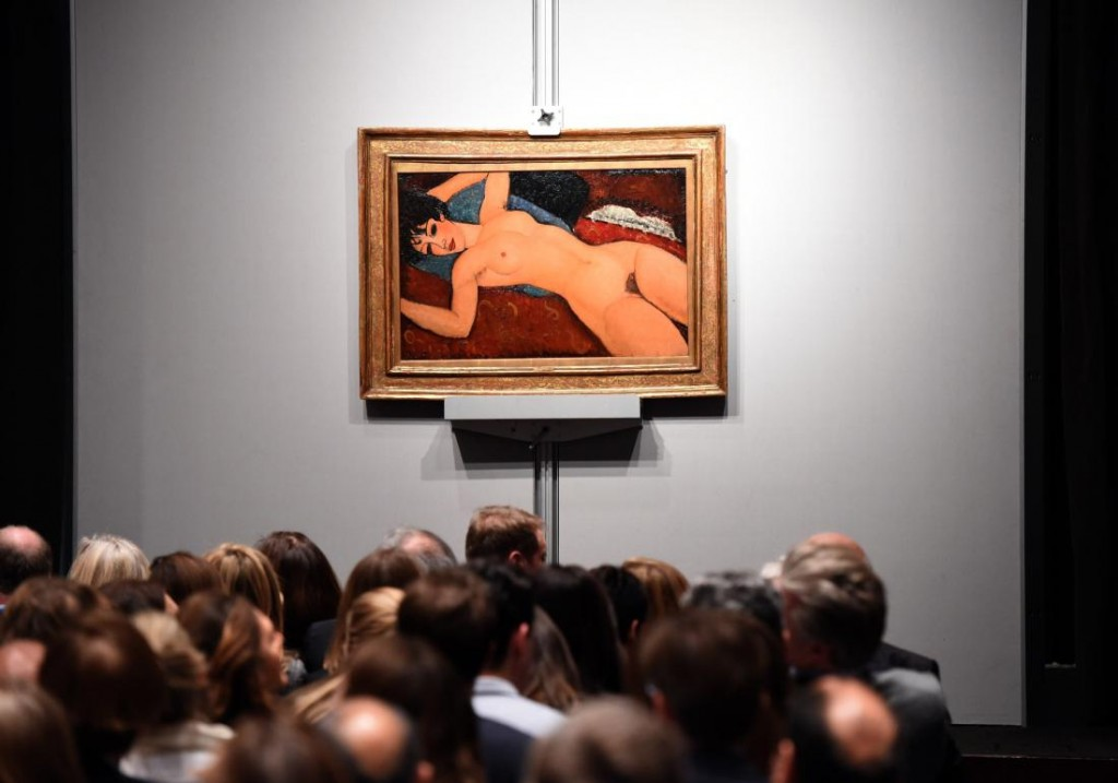 """Crowds sit in front of Amedeo Modigliani's """"Nu couche"""" during the """"Artist Muse: A Curated Evening Sale"""" November 9, 2015 at Christie's New York November 9, 2015. Image courtesy T.A. Clary / AFP / Getty Images."""